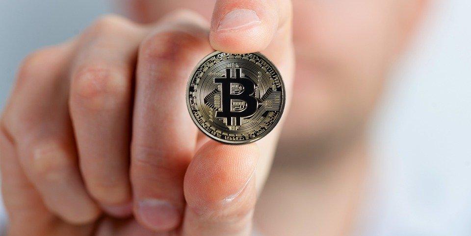 Bitcoin Münze in der Hand halten